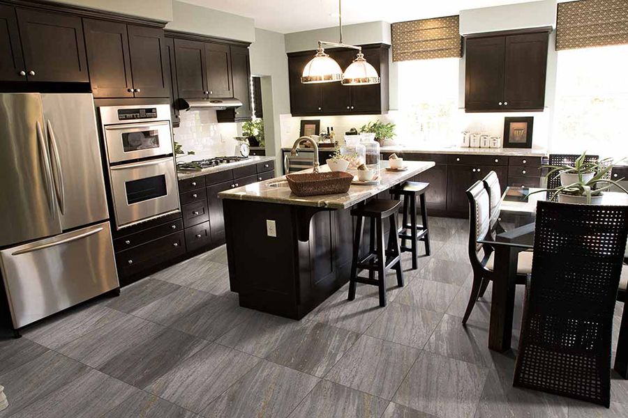 Kitchen with dark cabinets and grey luxury vinyl flooring that looks like stone